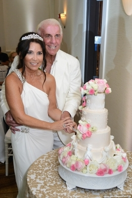 a person cutting a wedding cake: Congrats! Ric Flair, 69, added husband to his already stellar resume as he said 'I do' to Wendy Barlow, 58, during a star-studded ceremony at The Pearl Hotel in Rosemary Beach, Florida on Wednesday afternoon