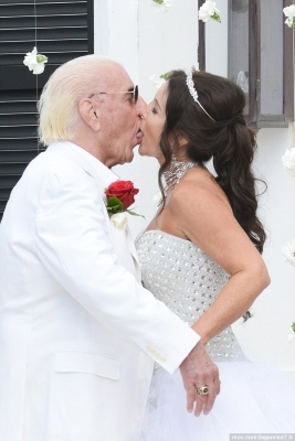 a person cutting a wedding cake: Official! The legendary performer reportedly walked down the aisle to the aptly named Offset and Metro Boomin song 'Ric Flair Drop' while wearing a custom white suit before sealing their union with a passionate kiss