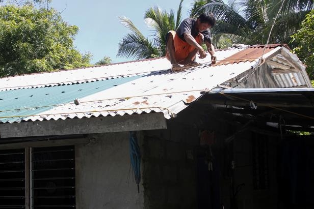 Slide 2 of 9: A resident secures the roof of his house in preparation for super typhoon Mangkut in Candon City, Ilocos Sur province, north of Manila on September 13, 2018. - A super typhoon roared toward the Philippines on September 13, packing fierce winds and heavy rains that are expected to strike the disaster-prone nation at the weekend before moving on to China.