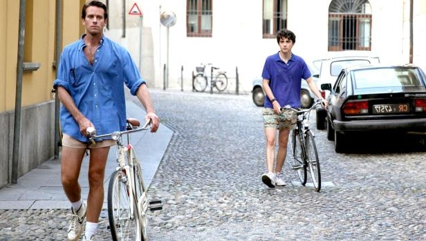 a man riding a bicycle on a city street: Call Me By Your Name