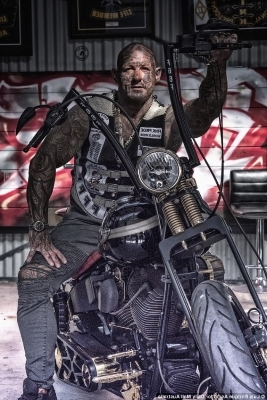a person sitting on a motorcycle: Th face-tattooed bikie boss (pictured) has been charged with numerous offences including aggravated home invasion, intention to cause injury, unlawful assault and threats to kill