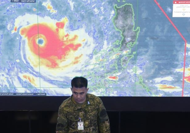 Slide 1 of 13: A member of the Philippine Air Force stands in front of a satellite image of Typhoon Mangkhut, locally named Typhoon Ompong, at the National Disaster Risk Reduction and Management Council operations center in metropolitan Manila, Philippines on Thursday, Sept. 13, 2018. Philippine officials have begun evacuating thousands of people in the path of the most powerful typhoon this year, closing schools and readying bulldozers for landslides. (AP Photo/Aaron Favila)