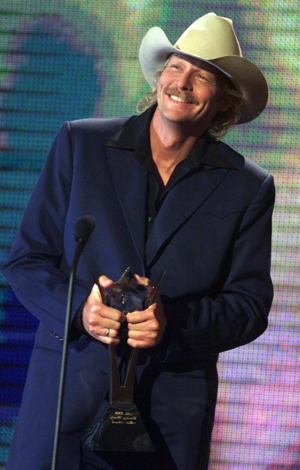 Slide 10 of 65: Alan Jackson is all smiles as he receives another one of his many awards during the TNN and CMT Country Weekly Awards show June 13, 2001.