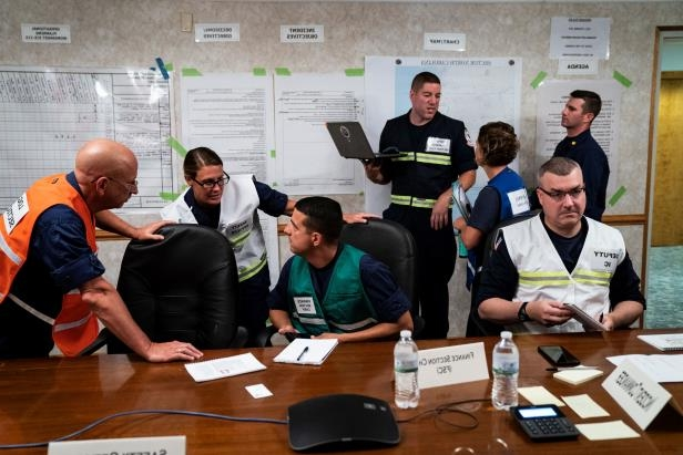 Slide 2 of 71: U.S. Coast Guard officers speak during the last command and staff meeting before Hurricane Florence reaches the East Coast at the U.S. Coast Guard Incident Command Post on Seymour Johnson Air Force Base on Thursday, Sept 13, 2018 in Goldsboro, NC.
