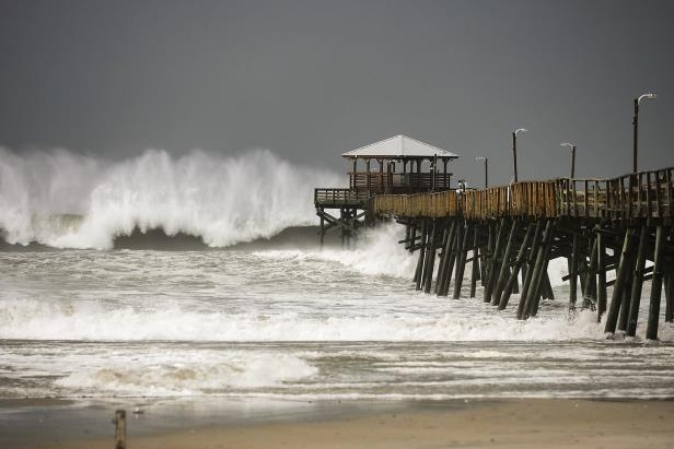 Slide 23 of 71: ATLANTIC BEACH, NC - SEPTEMBER 13:  Waves crash around the Oceana Pier as the outer edges of Hurricane Florence being to affect the coast September 13, 2018 in Atlantic Beach, United States. Coastal cities in North Carolina, South Carolina and Virgnian are under evacuation orders as the Category 2 hurricane approaches the United States. (Photo by Chip Somodevilla/Getty Images)