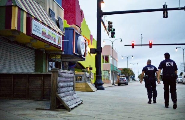 Slide 33 of 71: Police patrol past boarded up shops along the boardwalk in Myrtle Beach, S.C., Thursday, Sept. 13, 2018, as Hurricane Florence approaches the east coast. (AP Photo/David Goldman)