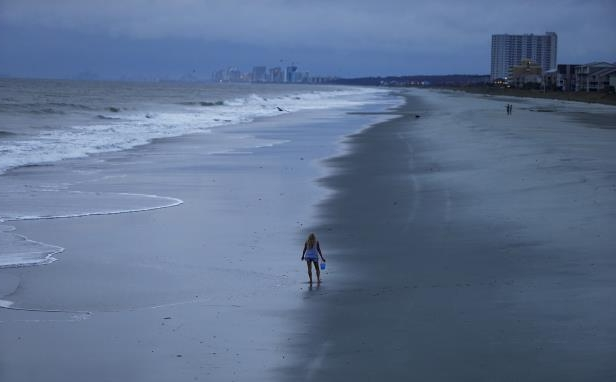 Slide 36 of 71: A woman looks for shells ahead of the arrival of Hurricane Florence in Surfside Beach, South Carolina, U.S. September 13, 2018.  REUTERS/Randall Hill      TPX IMAGES OF THE DAY - RC1A0D5AFD60