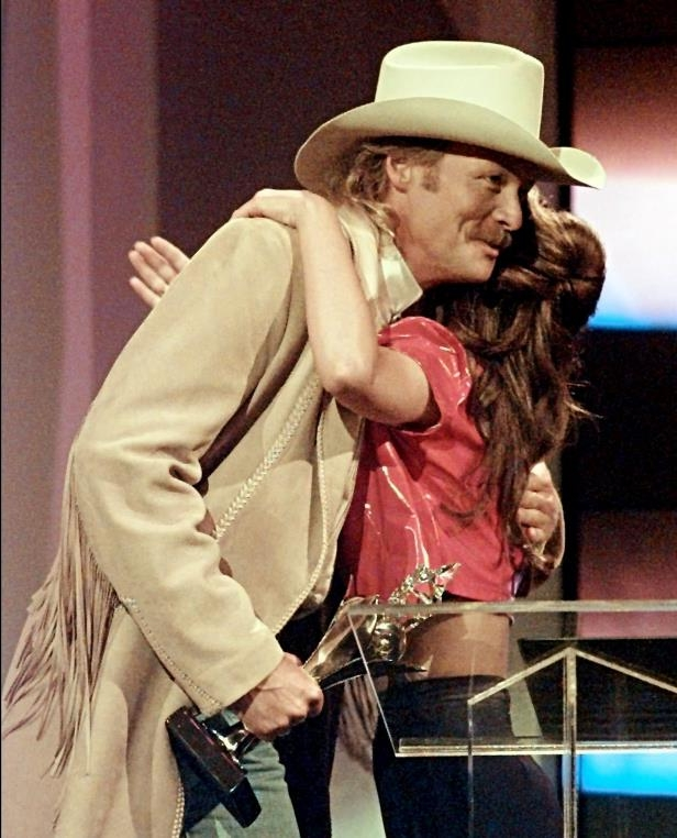 Slide 5 of 65: Alan Jackson gets a hug from presenter Shania Twain after he was named the Male Artist of the Year during the TNN Music City News Country Awards show June 10, 1996. Jackson also won the Entertainer of the Year award.