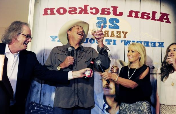 Slide 55 of 65: Country Music Hall of Fame and Museum director Kyle Young, right, gives a toast to Alan Jackson, who's wife, Denise and daughters were present during an opening party for Alan Jackson's exhibit in commemoration of his 25 years in country music Aug. 27, 2014.