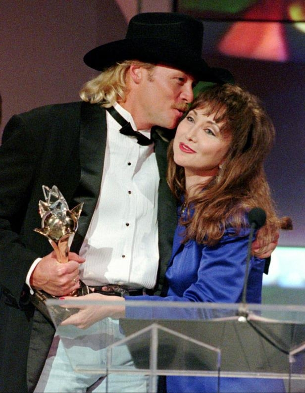 Slide 6 of 65: Alan Jackson, right, gets a hug along with a trophy from presenter Pam Tillis as he accepts the Single of the Year award during the TNN Music City News Country Awards show June 5, 1995, at the Grand Ole Opry. Jackson took home five awards for the night.