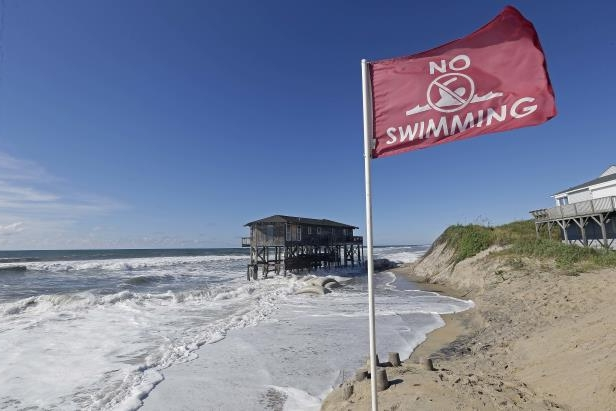 Slide 60 of 71: A warning flag flies as high tide surrounds an old cottage that has already succumbed to long-term beach erosion in Nags Head, N.C., Wednesday, Sept. 12, 2018 as Hurricane Florence approaches the coast of the Carolinas. The National Weather Service says Hurricane Florence