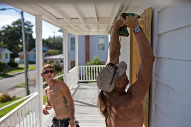 Slide 68 of 71: Tom Thompson and Wil McComas work to board up a historic home in Swansboro, N.C. on Sept. 12, 2018 in advance of Hurricane Florence. - Hurricane Florence churned across the Atlantic Ocean on Wednesday packing winds of 130 miles per hour (215 kph) as an emergency management official warned the monster storm would deliver a