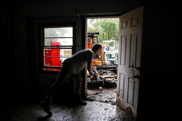 Slide 1 of 134: People clean their house after the pass of Hurricane Florence in New Bern, North Carolina, U.S., September 16, 2018. REUTERS/Eduardo Munoz