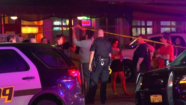 a group of people standing on top of a car: The shooting was prompted by a fight at about 12:20 a.m. outside the Pegasus bar in the 1400 block of North Main Avenue. Two suspects involved in the fight got into a red Nissan sedan, and opened fire on a crowd of people as they sped away.