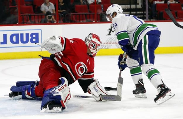Carolina Hurricanes goaltender Curtis McElhinney (35) tries to block the  shot of Vancouver Canucks b7694bdd7