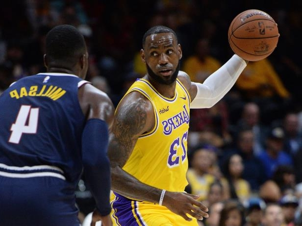 a basketball player with a football ball: NBA: Preseason-Denver Nuggets at Los Angeles Lakers