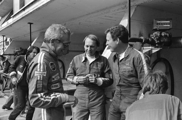 a group of people in uniform: The Whittingtons, Don (left) and Bill (center) chat with actor/racer Paul Newman at Le Mans, 1979.