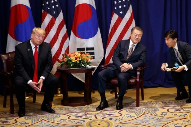 a group of people posing for the camera: President Moon Jae-in of South Korea, center, with President Trump in New York in September.