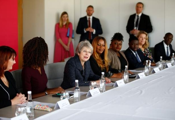 a group of people sitting at a table: Britain's Prime Minister Theresa May attends a roundtable meeting with business leaders, whose companies are inaugural signatories of the Race at Work Charter, at the Southbank Centre in London