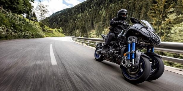 a person riding a motorcycle on the side of a road: The Yamaha Niken is a three-cylinder, 115-hp motorcycle with an extra front wheel to increase traction through turns.