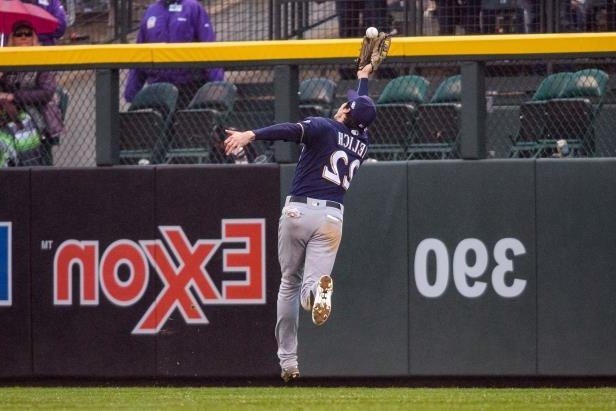 Slide 16 of 47: Denver, CO - OCTOBER 07: Milwaukee Brewers outfielder Christian Yelich (22) attempts to make a catch during the Milwaukee Brewers vs Colorado Rockies National League Division series game 3 at Coors Field on October 7, 2018 in Denver, CO.