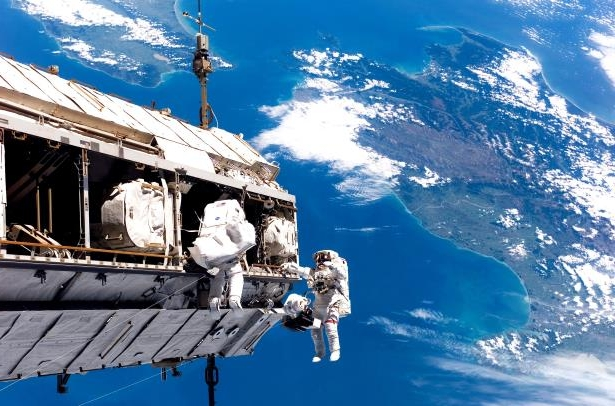Slide 17 of 98: Backdropped by the islands of New Zealand, astronaut Robert Curbeam Jr., left, and European Space Agency astronaut Christer Fuglesang of Sweden, participate in an STS-116 spacewalk on Dec. 12, 2006. The extravehicular activities in support of construction of the International Space Station were crucial in assembly of elements such as the truss segment delivered by the space shuttle Discovery.