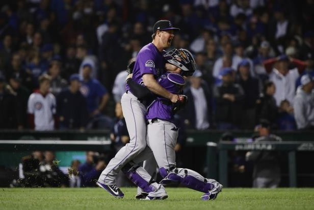 Slide 42 of 47: CHICAGO, IL - OCTOBER 02:  Scott Oberg #45 and Tony Wolters #14 of the Colorado Rockies celebrate defeating the Chicago Cubs 2-1 in thirteen innings to win the National League Wild Card Game at Wrigley Field on October 2, 2018 in Chicago, Illinois.  (Photo by Jonathan Daniel/Getty Images)