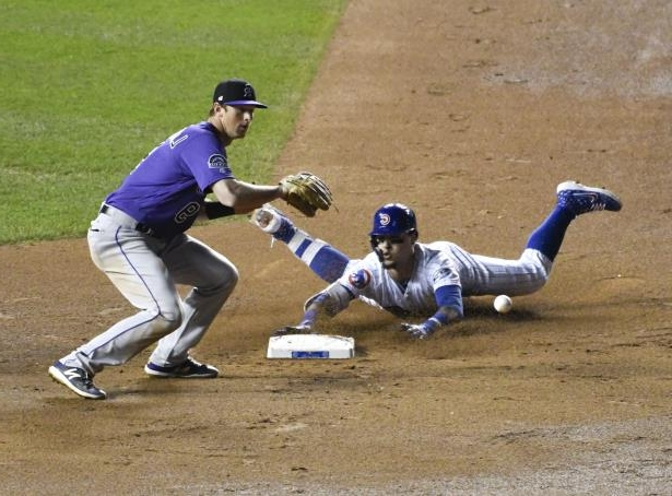 Slide 45 of 47: Chicago Cubs' Javier Baez, left, slides into second base safely as he hit a one-run double as Colorado Rockies second baseman DJ LeMahieu (9) makes a late tag during the eighth inning of the National League wild-card playoff baseball game, Tuesday, Oct. 2, 2018, in Chicago. (AP Photo/David Banks)