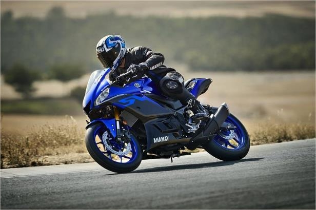 a man riding a motorcycle down a dirt road: 2019 Yamaha YZF-R3