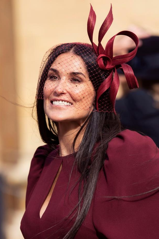 a woman wearing a red hat: Demi Moore leaves St. George's Chapel at Windsor Castle following Princess Eugenie of York and Jack Brooksbank's wedding on Oct. 12, 2018.