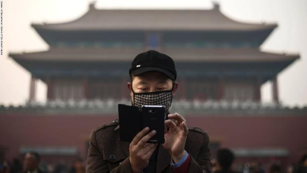 BEIJING, CHINA - NOVEMBER 20: A Chinese man wears a mask to protect against pollution as he uses his smartphone on a hazy day outside the Forbidden City November 20, 2014 in Beijing, China. United States President Barack Obama and China's president Xi Jinping agreed on a plan to limit carbon emissions by their countries which are the world's two biggest polluters at a summit in Beijing last week. (Photo by Kevin Frayer/Getty Images)