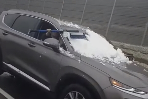 Watch This Clueless Driver Clear Her Windshield of Snow on a Busy Highway