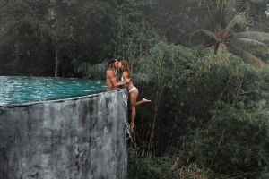 A travel influencer couple has defended a 'terrifying' Instagram stunt which involved hanging off the edge of an infinity pool