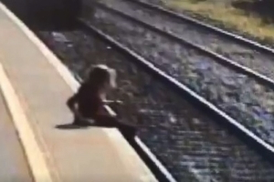 Woman's lucky escape as video shows her noticing oncoming train milliseconds before it was about to plough through her legs
