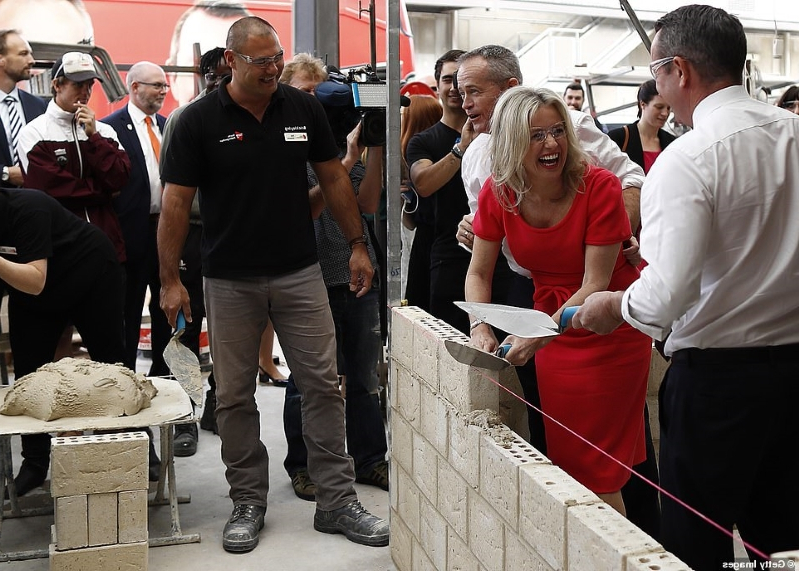 Not afraid to get her hands dirty! Chloe Shorten mucks in as she helps Bill build a wall with apprentice tradies on the campaign trail