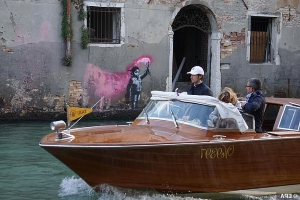 Suspected Banksy of a migrant child in a life-jacket holding a flare appears on the side of a canal in Venice