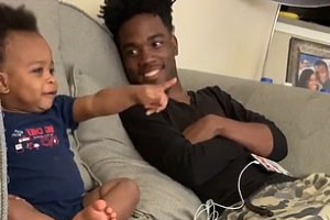 Father and son have an animated 'conversation' while watching television together