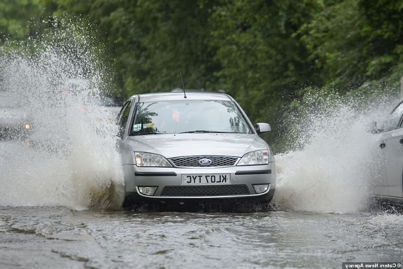 'Summer, why have you forsaken us?': Drenched Brits are driven to despair as a fourth day of 'treacherous' flash floods leaves motorists stranded in their cars and train tracks submerged