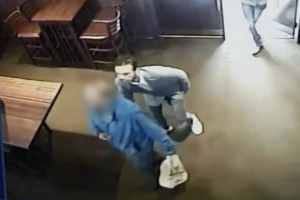 CCTV shows an alleged pickpocket reaching for an elderly man's jacket in an Irish pub