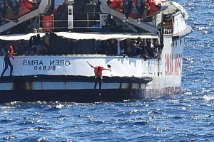Migrants 'going mad' jump in sea in desperate bid to reach Italy