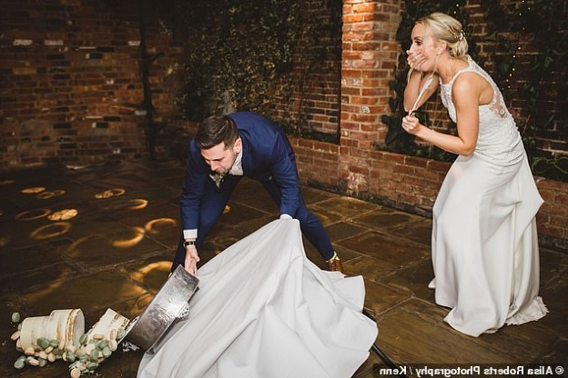 Newlyweds look on in horror as the table holding their three-tier wedding cake collapses and the $550 creation topples to the floor