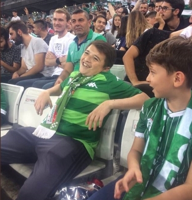 Revealed: Smoking 'child' at Turkish football match is actually a 36-year-old MAN who has amazed the world with his 'Benjamin Button' appearance (and he's sitting next to his son)