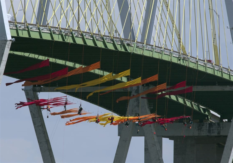 Greenpeace activists suspend themselves from a Houston bridge hours before the debate