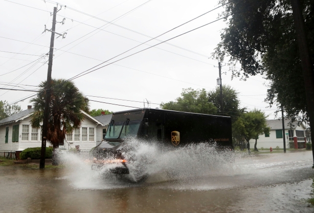 Slide 13 of 18: A United Postal Service truck creates a wake as Tropical Depression Imelda continues to rain in Galveston, Texas on Sept. 18, 2019.