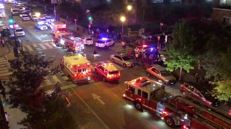 a car driving on a city street filled with lots of traffic: Rescue vehicles are seen following a shooting in Washington