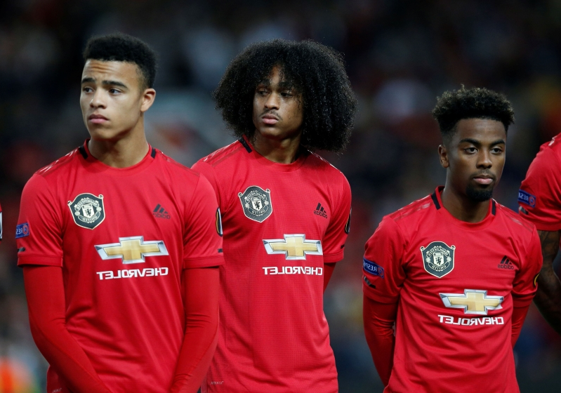a group of football players posing for a picture: Soccer Football - Europa League - Group L - Manchester United v Astana - Old Trafford, Manchester, Britain - September 19, 2019 Manchester United's Angel Gomes, Tahith Chong and Mason Greenwood lined up before the match  REUTERS/Andrew Yates