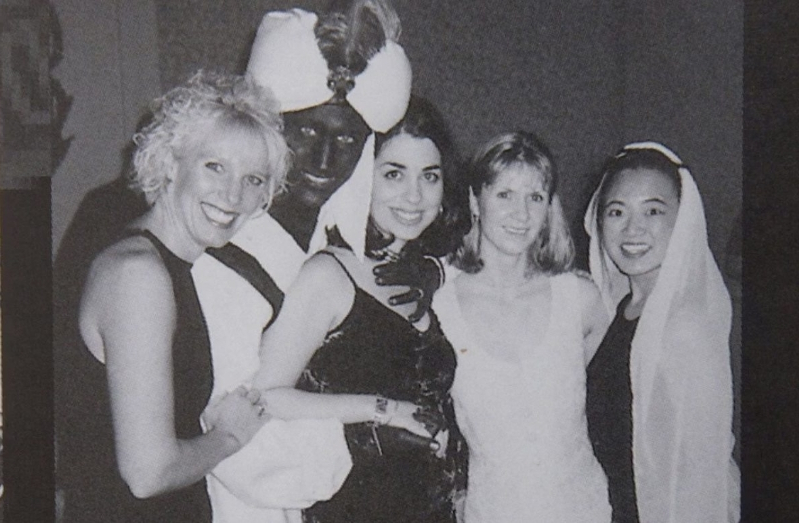 a group of people posing for a photo: A photo showing Prime Minister Justin Trudeau, second from right, at a 2001 costume party - his hands and face blackened with makeup -- was published by Time Magazine Wednesday. They say it was published in the yearbook from the West Point Grey Academy, a private school in Vancouver, B.C., where Trudeau worked as a teacher before entering politics.