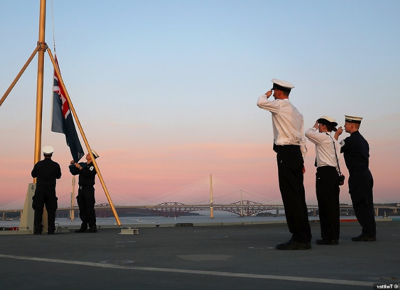 a group of people posing for the camera: At 8pm it was announced that the carrier was at anchor in the Forth to conduct more checks and training before sailing under the forth bridges in the near future. They HMS Prince of Wales Twitter account posted the above image saying: 'First sunset ceremony complete. A fantastic end to a historic day for @HMSPWLS'