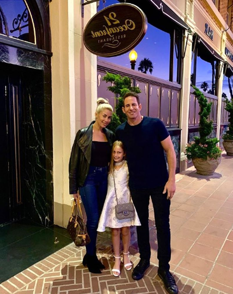 a group of people standing in front of a building: Tarek El Moussa, Heather Rae Young, and Taylor | Tarek El Moussa Instagram