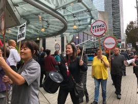 a group of people standing in front of a crowd: Workers from the Hyatt Regency Vancouver participate in a picket action on Friday, Sept. 13.